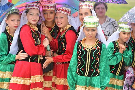 Para anak-anak perempuan Rusia dengan pakaian nasional ini ikut serta dalam perayaan hari libur orang Tatar Sabantuy 2015 di Troitsk. Foto: RIA Novosti