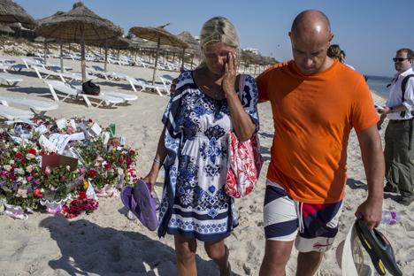 Seorang turis menahan tangis setelah memberikan penghormatan pada tempat peringatan sementara di resor tepi pantai Imperial Marhaba, yang diserang oleh seorang pria bersenjata di Sousse, Tunisia (29/6). Sang penembak yang menyamar sebagai turis menembaki orang-prang di Hotel Tunisia Jumat lalu dengan senapan yang ia sembunyikan di balik payung. Aksi terorisme tersebut menewaskan 39 orang termasuk warga Inggris, Jerman, dan Belgia saat mereka sedang bersantai di pantai ketika serangan yang diklaim dilakukan oleh ISIS tersebut terjadi. Foto: Reuters