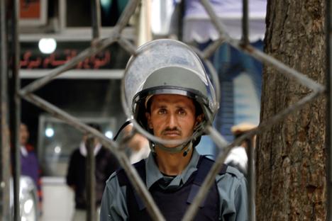 Seorang Polisi Nasional Afghanistan sedang menjaga keamanan selama berlangsungnya protes terhadap kurangnya upaya pemerintah mencari sekelompok orang dari kelompok minoritas masyarakat Afghanistan Hazara Syiah yang diculik pada bulan Februari lalu, di Kabul, Afghanistan. Foto diambil pada bulan April 2015. Foto: AP