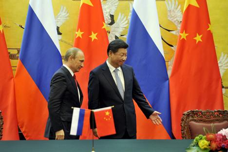 Presiden Tiongkok Xi Jinping mempersilakan Presiden Rusia Vladimir Putin setelah upacara penandatangan di Balai Agung Rakyat di Beijing, Tingkok (3/9).
