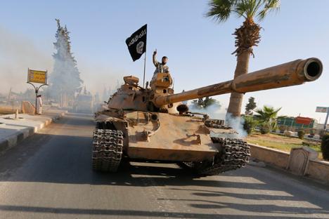 "Para pejuang militan Islam di atas tank ikut serta parade militer di sepanjang jalan di utara Provinsi Raqqa pada 30 Juni 2014. Para pejuang Islam militan ini mengadakan parade untuk merayakan deklarasi mereka atas pembentukan ""khilafah"" Islam setelah kelompok ini ditangkap di wilayah negara tetangga mereka, Irak."