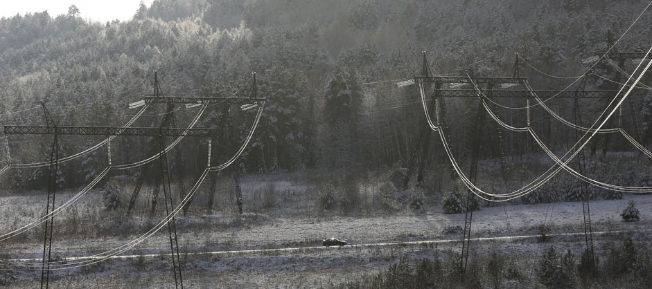 A car drives under high voltage power lines from Krasnoyarskhydroelectric power station, south of the Siberian city ofKrasnoyarsk, Russia, October 24, 2015. The 500-kilovolt line supplieselectricity to the Krasnoyarsk aluminium smelter and other industriesin Siberia.