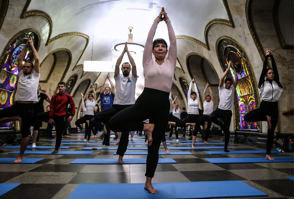 "Russia. Moscow. November 29, 2015. Residents of the city during the yoga on the ring metro station ""Novoslobodskaya""."