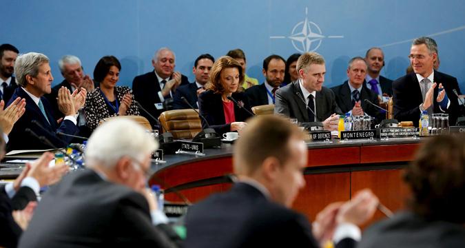Menteri Luar Negeri AS John Kerry (kiri) dan Sekretaris Jenderal NATO Jens Stoltenberg (kanan) memuji pernyataan Menteri Luar Negeri Montenegro Igor Luksic setelah Montenegro disambut sebagai anggota baru di pertemuan tingkat menteri NATO di markas NATO di Brussels, 2 Desember, 2015.