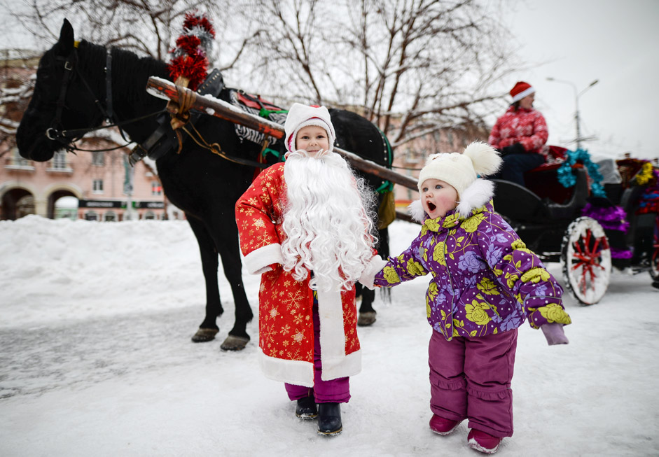 Children near a horse-drawn cart during the Father Frost Parade in the Dzerzhinsky district of Novosibirsk.