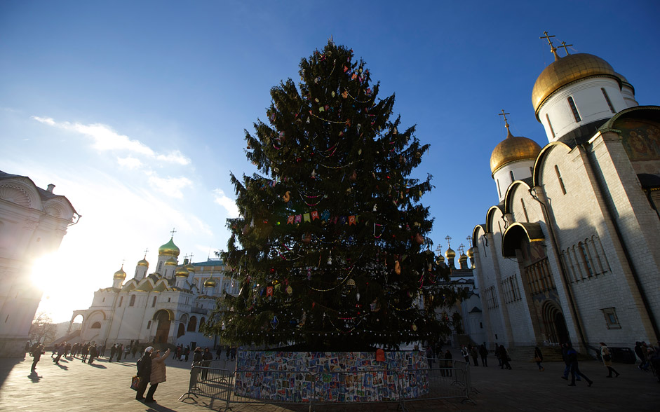 A New Year tree is installed for New Year and Christmas celebrations in Cathedral Square in the Kremlin in Moscow, Russia, on Tuesday, Dec. 29, 2015. Orthodox Christians celebrate Christmas on Jan. 7, in accordance with the Julian calendar. At right is the Assumption Cathedral.