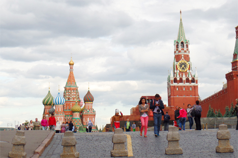Dua orang turis berjalan dari arah Katederal St. Basil (kiri) dan Menara Spasskaya di Lapangan Merah menuju Lapangan Revolusi di Moskow, Rusia.