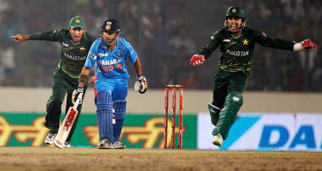 Pakistan's Umar Akmal, right, and Nasir Jamshed, left, celebrate the dismissal of India's Gautam Gambhir, center, during their Asia Cup cricket match in Dhaka, Bangladesh, Sunday, March 18, 2012. Source: AP