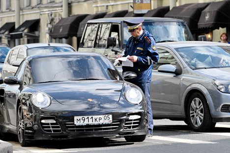 Russia's road police officer looking through the documents of a driver. Source: ITAR-TASS