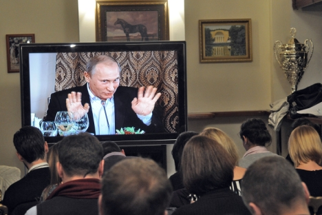 Vladimir Putin speaking from a TV screen during a Valdai club discussion. Source: Kommersant