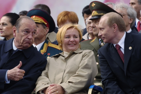 French President Jacques Chirac (left) gives the thumbs up to Russian President Vladimir Putin while Putin's wife Lyudmila smiles during the Victory Day parade on May 9, 2005. Source: AP