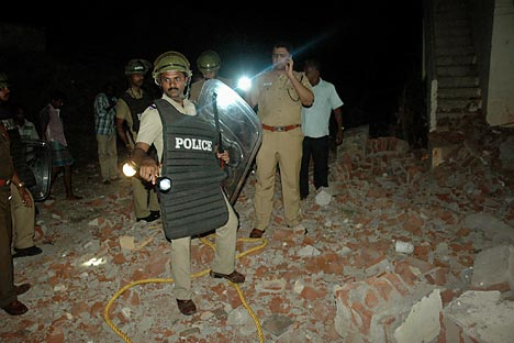 Indian policemen inspect the blast site after a crude bomb went off near the Kudankulam Nuclear Power Plant in Idinthakarai coastal village. Source: AP