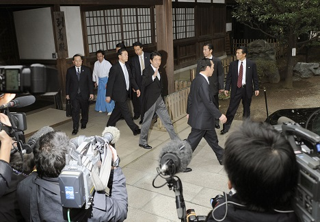 Prime Minister Shinzo Abe (raising hand) leaves Yasukuni Shrine in Tokyo on Dec. 26, 2013 after paying homage there. Source: Photoshot / Vostock-photo