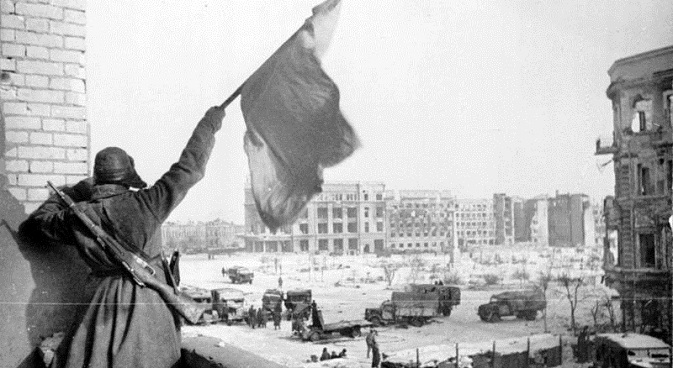 Soviet soldier waving the Red Banner over the central plaza of Stalingrad in 1943. Source: Deutsches Bundesarchiv / wikipedia