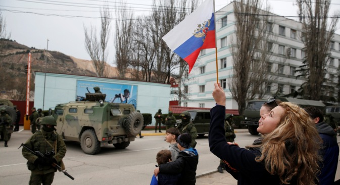 A woman waves a Russian flag as armed servicemen wait near Russian army vehicles outside a Ukrainian border guard post in the Crimean town of Balaclava March 1, 2014. Source: Reuters