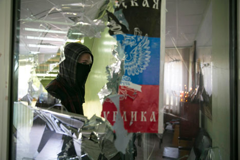 Masked man walks past a broken window inside the Mariupol town hall in east Ukraine April 26, 2014. Source: Reuters