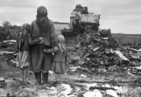 A woman and two girls looking at their destroyed house, USSR, 1943. Source: RIA Novosti