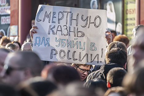 A Belgorod resident holds up a poster demanding capital punishment for those guilty of murder, at the site of a shooting incident on Narodny Bulvar in Belgorod. Six people were killed in the incident. Source: Alexandr Urivskiy / RIA Novosti