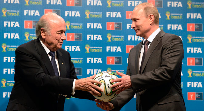 FIFA President Sepp Blatter and Russian President Vladimir Putin hold a soccer ball during the official ceremony of handover to Russia as the 2018 World Cup hosts, July 13, 2014. Source: AP