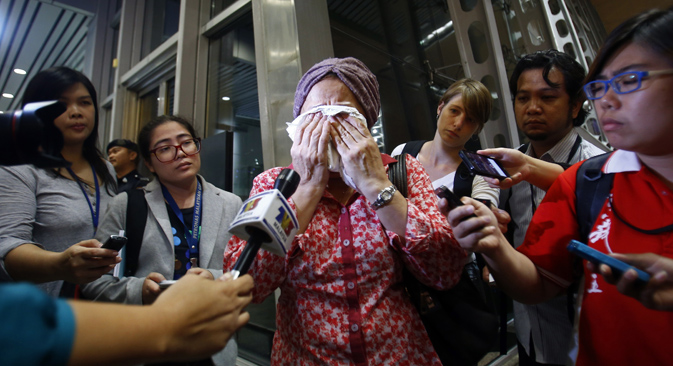 TV journalists try to interview a crying woman as she waits more information about the Malaysian Boeing 777 after it was shot down. Source: Reuters