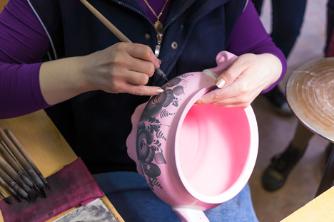 Gzhel artist at work on a vase at a Gzhel facility, manufacturing Russian folk art porcelain. Source: Lori/Legion Media