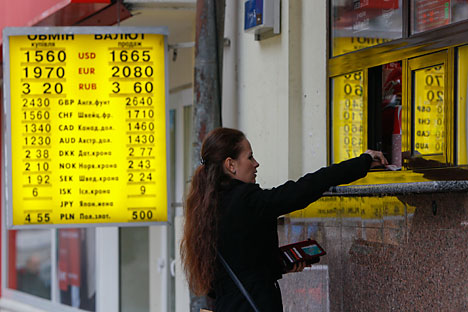 A woman hands over money to a shop employee near a board showing currency exchange rates in Kiev November 12, 2014. Ukraine's central bank said on Wednesday it may soften its policy on mandatory sales of foreign currency income on the domestic market, to encourage companies to bring more dollars into the country. Source: Reuters