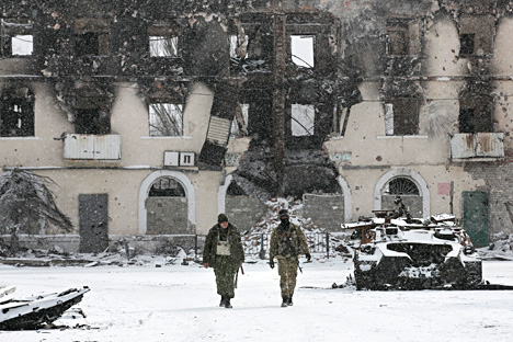 Fighters of the self-proclaimed Donetsk People's Republic walk past a destroyed Ukrainian army armoured personnel carrier in the town of Vuhlehirsk, about 10 km (6 miles) to the west of Debaltsevo, Feb. 16. Source: Reuters