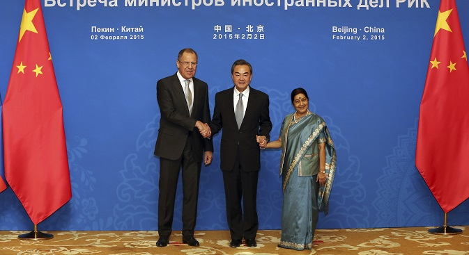 Sergey Lavrov (l), Wang Yi (c) and Sushma Swaraj shake hands together as they pose for photographers before the meeting of the Foreign Ministers of the China, Russia and India in Beijing on February 2, 2015. Source: AP