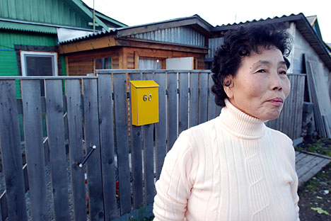 Pak Den Dya, an ethnic Korean living on Russia's Sakhalin Island, poses in front of her home in Yuzhno-Sakhalinsk, Russia. Source: AP Photo/Burt Herman