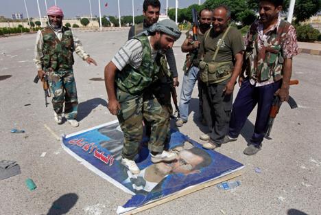 Seroang anggota Tentara Pembebasan Suriah menginjak foto Presiden Suriah Bashar al-Assad.