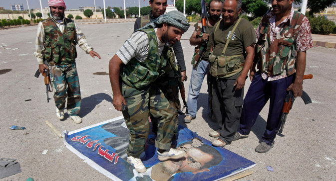 A Free Syrian Army fighter from the Al-Faruk brigade, center, steps on a portrait of Syrian President Bashar Assad