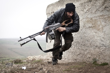 A Free Syrian Army fighter takes cover during fighting with the Syrian Army in Azaz, Syria.