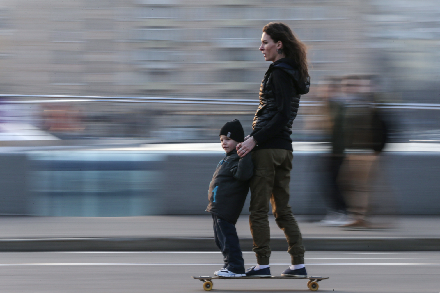 A woman and a kid skateboarding on Pushkinskaya Embankment in Moscow.