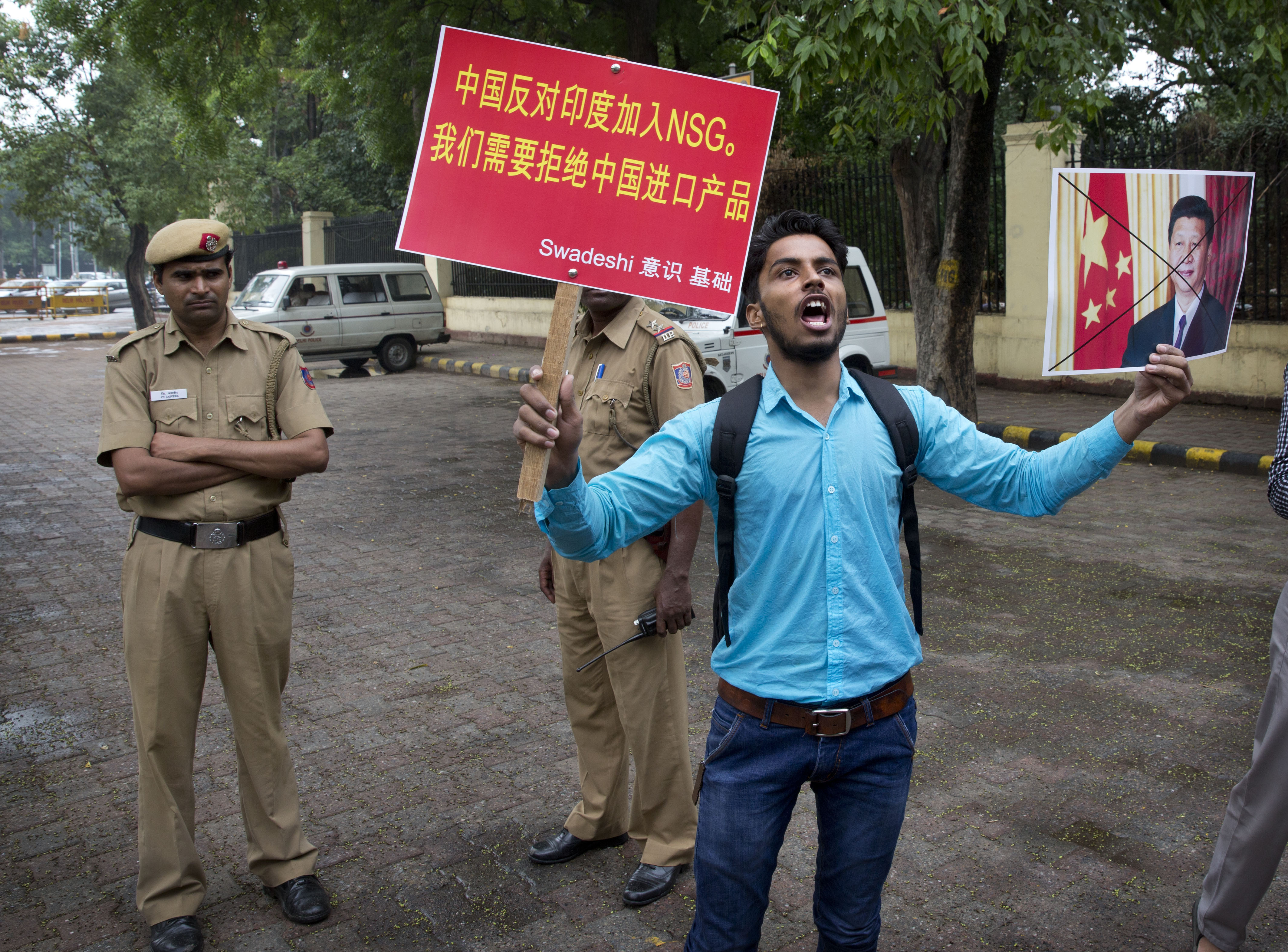 An activist holds a portrait of Chinese President Xi Jinping and shouts slogans during a protest near the Chinese embassy in New Delhi, June 28, 2016.