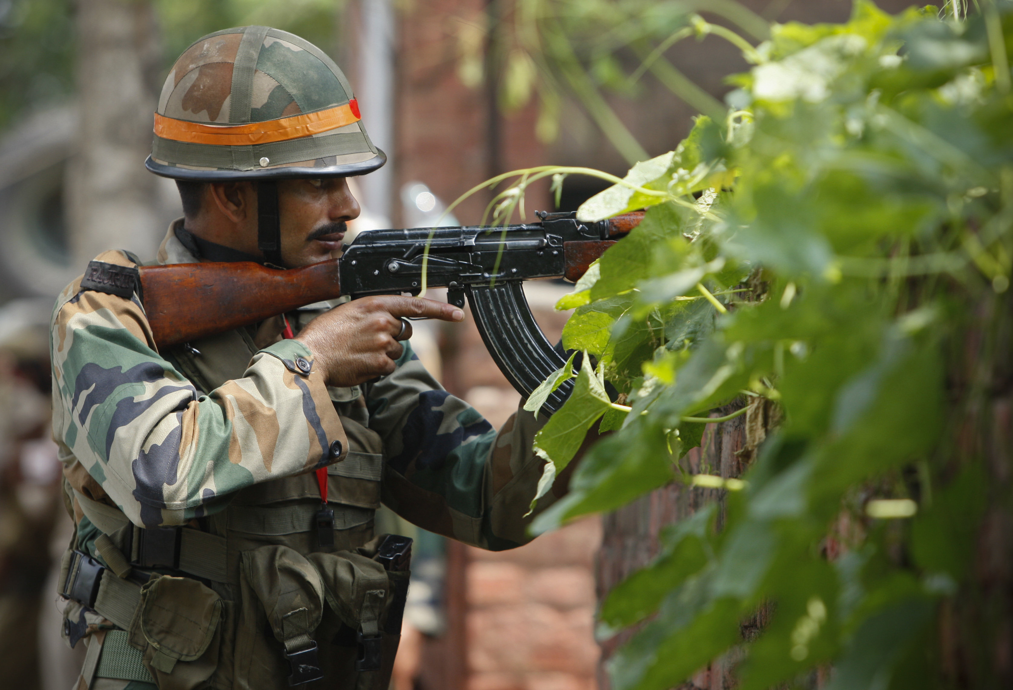 An Indian army soldier holds an AK-47 assault rifle during a fight in the town of Dinanagar, in the northern state of Punjab, India, Monday, July 27, 2015.