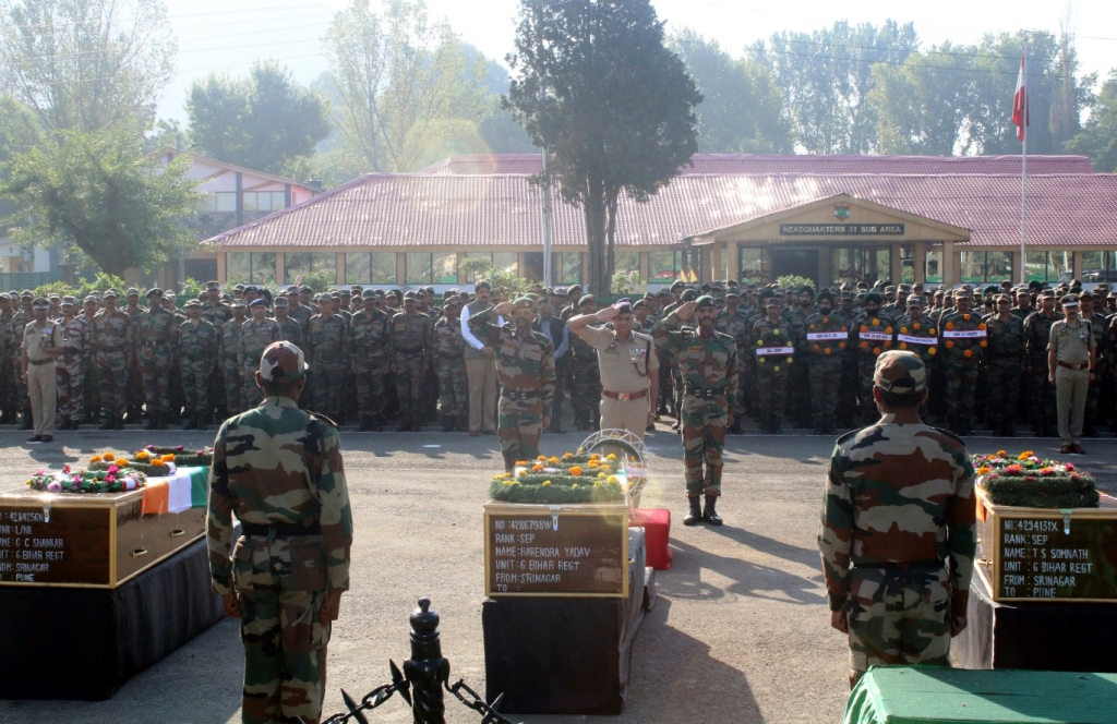Director General of Jammu and Kashmir Police, K Rajendra Kumar (C) salutes near the coffins containing bodies of Army soldiers during a wreath laying ceremony at Badami Bagh Cantonment, the Indian Army's headquarters in Srinagar, 19 September 2016.