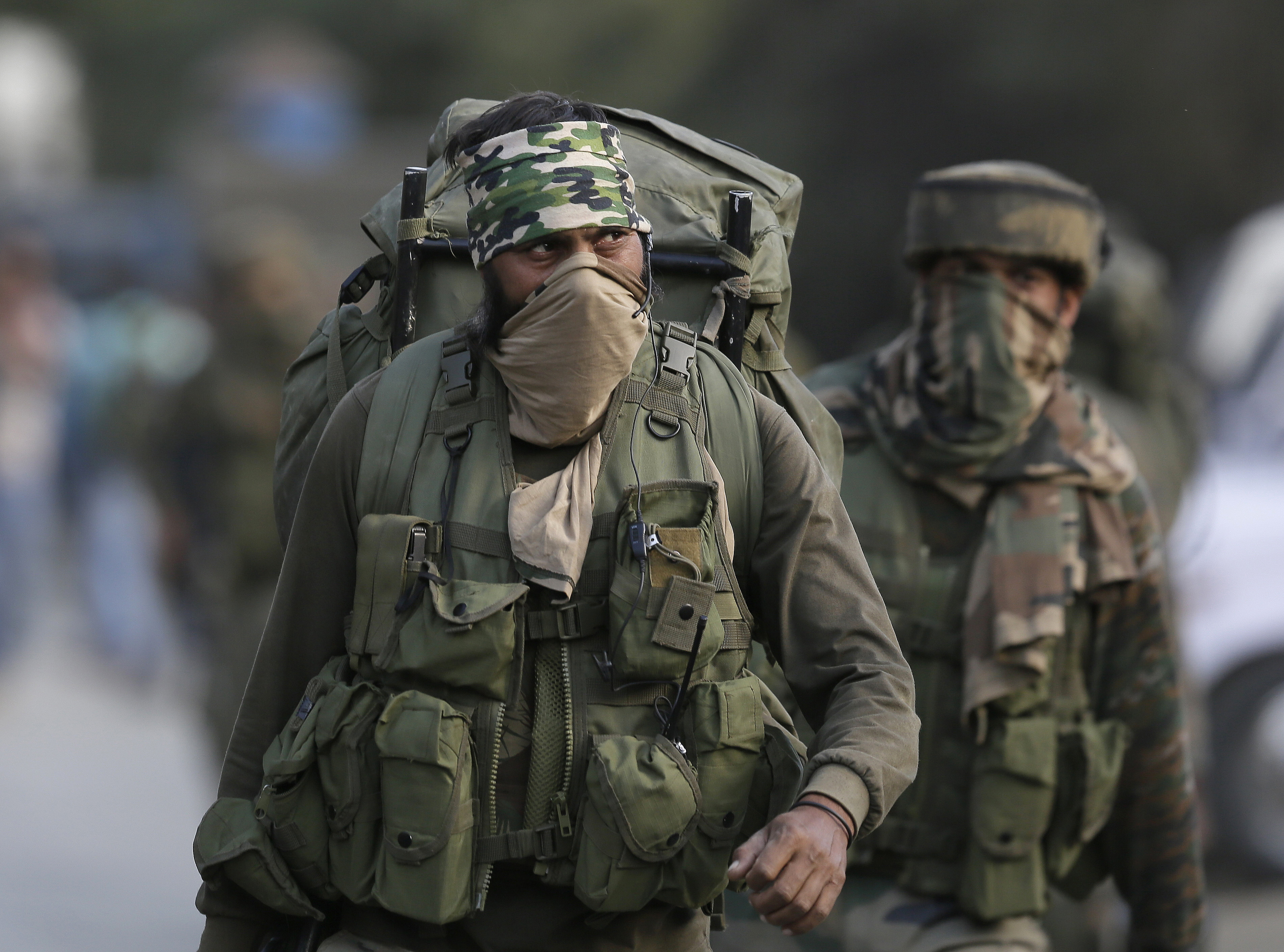 Indian Army soldiers leave the site of a gun battle in Pampore, on the outskirts of Srinagar, Kashmir.