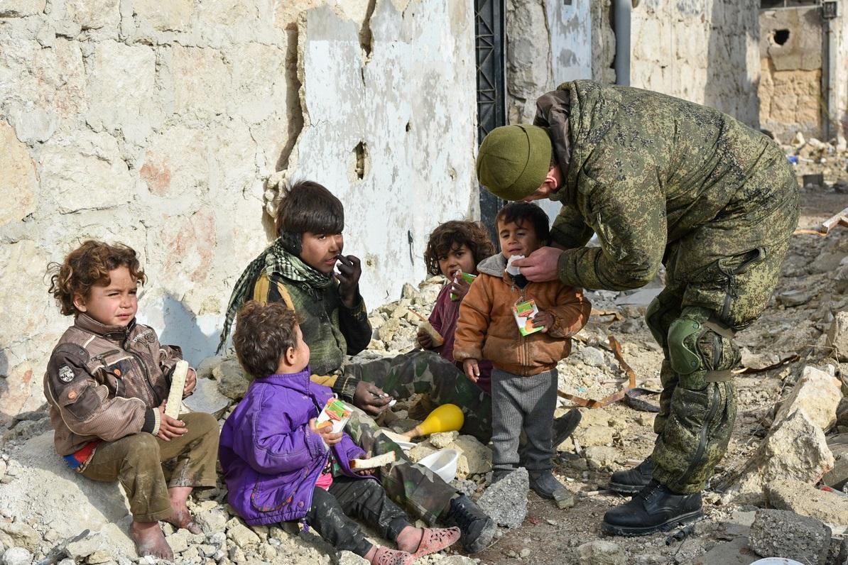 Seorang tentara Rusia tengah membersihkan mulut seorang anak Suriah di antara teman-temannya yang duduk di sekitar puing-puing bangunan.
