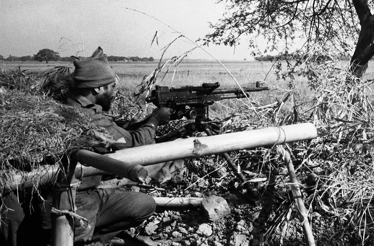 An Indian Army machine gunner fires at Pakistani positions in a village across an open field, 1,500 yards inside the East Pakistan border at Dongarpara on Dec. 7, 1971.