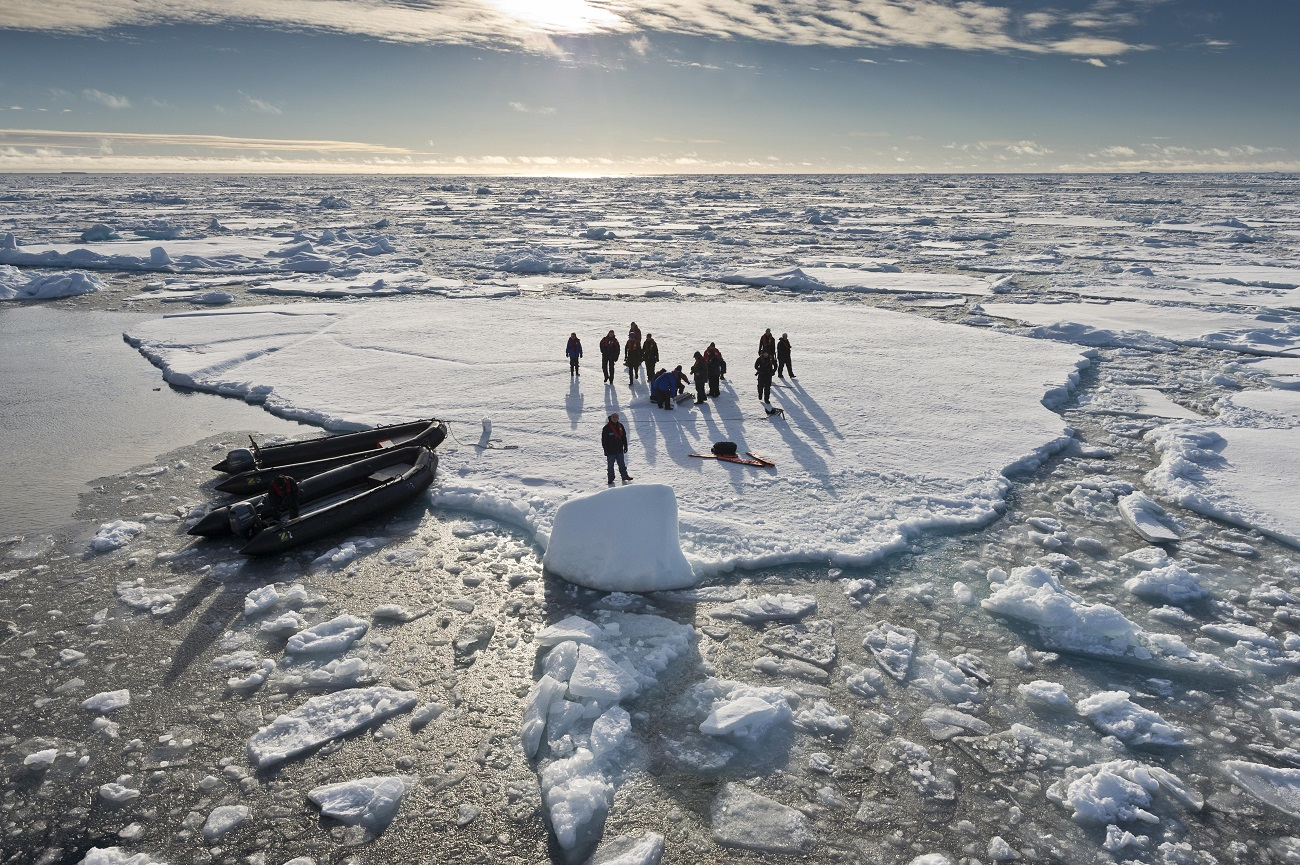 Tourists taken in inflatable boats onto an ice floe, pack ice, Spitsbergen Island, Svalbard Archipelago.