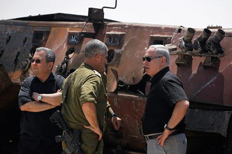 Il primo ministro isaeliano Benjamin Netanyahu (a destra) e il ministro della Difesa Ehud Barak di fronte a un veicolo militare egiziano bruciato,appena fuori dal Sud della Striscia di Gaza il 6 agosto 2012 (Foto: Reuters/VostokPhoto)