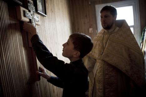 Fedor aiuta suo padre, prete ortodosso, durante il servizio della domenica, nel villaggio di Bagan, nella regione di Novosibirsk, 2011 (Credit: Valerij Klamm)