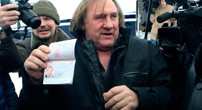 L'attore Gérard Depardieu mostra ai fotografi il passaporto russo (Foto: Reuters/VostockPhoto)