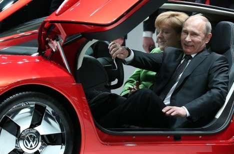 Il Presidente russo Vladimir Putin posa all'interno dell'auto ibrida Volkswagen XL 1,  alla fiera delle tecnologie industriali di Hannover (Germania), l'8 aprile 2013, con la cancelliera Angela Merkel (Foto: AFP / East News)
