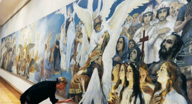 """Un'addetta osserva il disegno preliminare per la """"Gioia giusta di Dio. Trittico"""", alla mostra di Viktor Vasnecov alla Galleria Tretyakov (Foto: RIA Novosti / Vladimir Vyatkin)"""