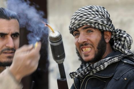 Combattenti dell'unità Tahrir al-Sham dell'Armata libera siriana lanciano una granata contro l'esercito di Damasco (Foto: Reuters)
