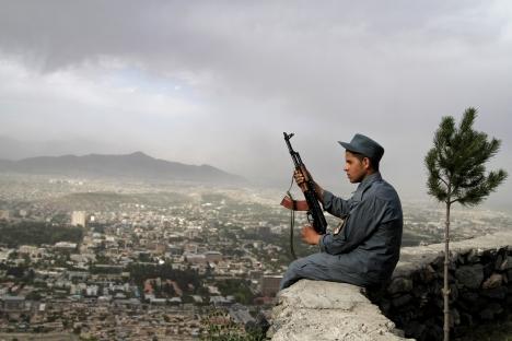 Un poliziotto afghano siede di guardia su un muro che domina Kabul (Foto: AP)