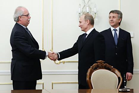 Il Presidente russo Vladimir Putin, al centro, stringe la mano al numero uno di Total, Christophe de Margerie, durante un incontro con il capo del Cremlino a Mosca (Foto: AFP / East News)