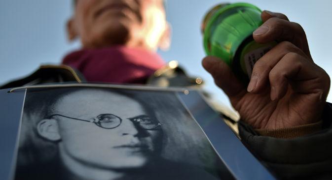 In occasione della manifestazione in memoria delle vittime, che si tiene tutti gli anni in Piazza Lubjanka a Mosca, un uomo regge il ritratto del padre morto durante il periodo della repressione politica (Foto: AFP/East News)