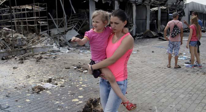Continuano gli scontri nel Donbass. Una donna si allontana da un edificio distrutto con la figlia in braccio (Foto: Reuters)